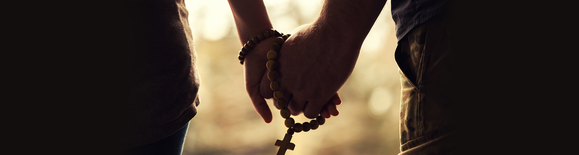 two people holding hands and rosary